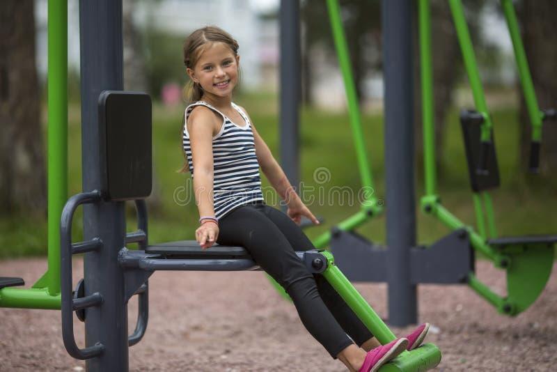 Petite fille mignonne sur le terrain de jeu sport photographie stock libre de droits