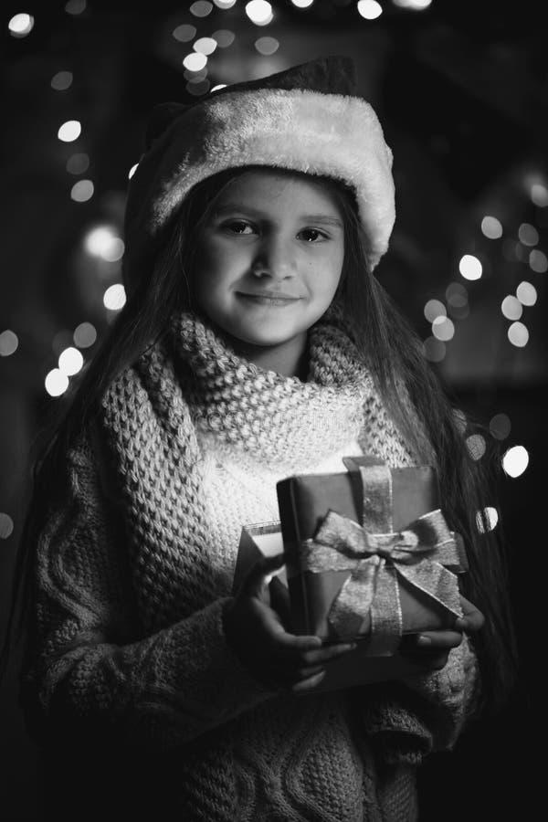Petite fille mignonne tenant le boîte-cadeau rougeoyant de Noël images libres de droits