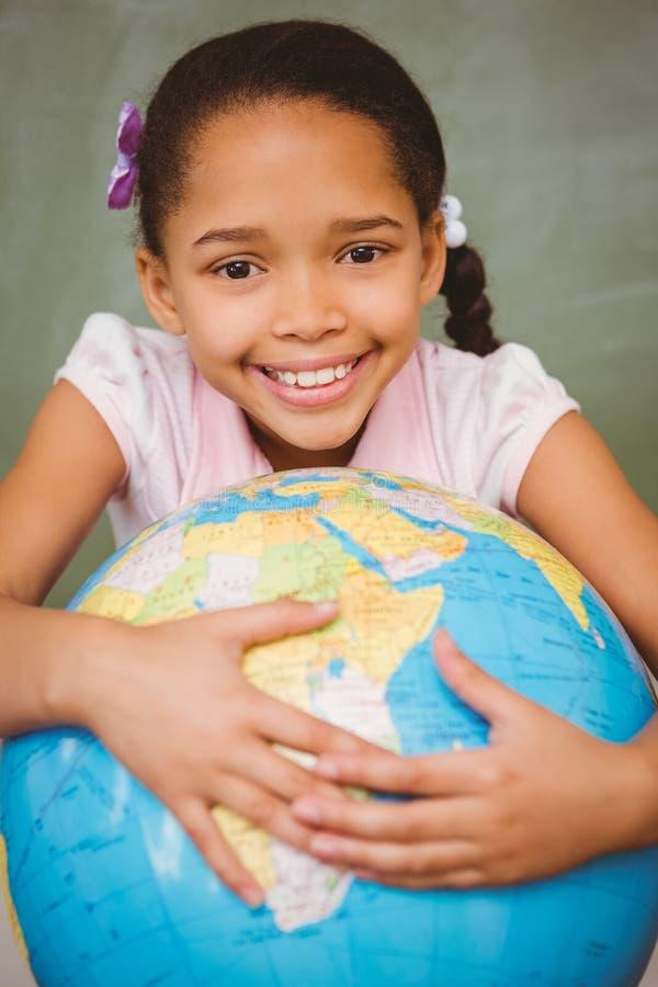 Petite fille mignonne tenant le globe image stock
