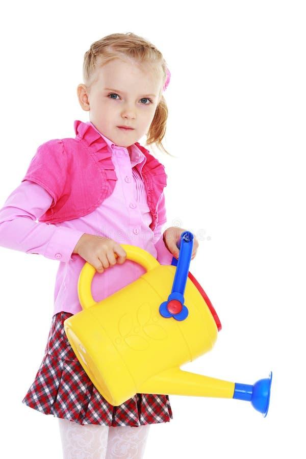 Petite fille mignonne tenant une boîte d'arrosage image libre de droits