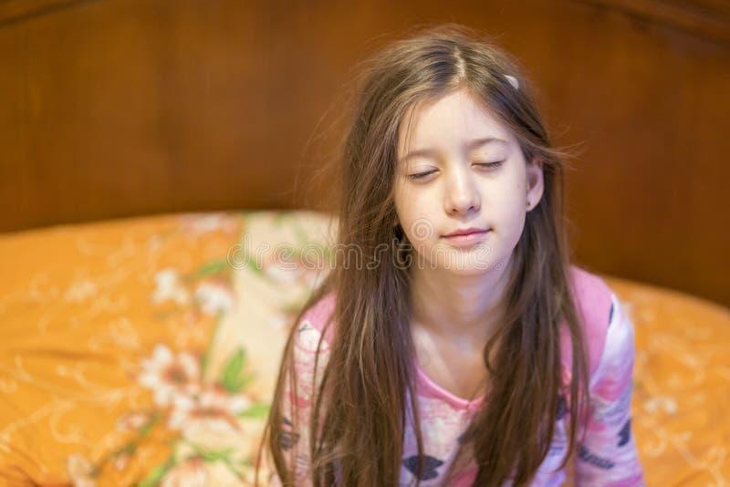 Petite fille mignonne ?tirant ses bras heureusement avec un sourire de se r?veiller dans son lit Ba?llement somnolent d'enfant da photo stock