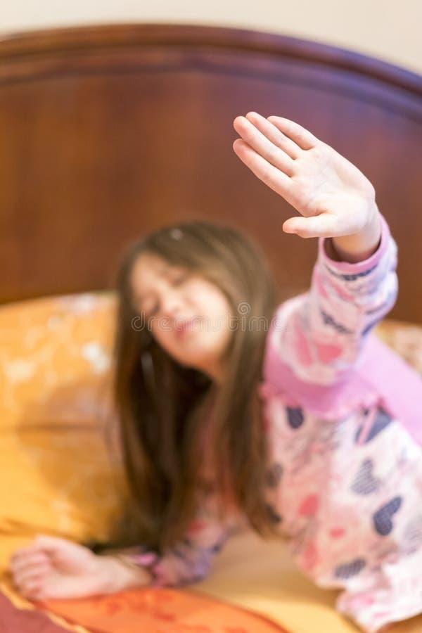 Petite fille mignonne ?tirant ses bras heureusement avec un sourire de se r?veiller dans son lit Ba?llement somnolent d'enfant da image stock