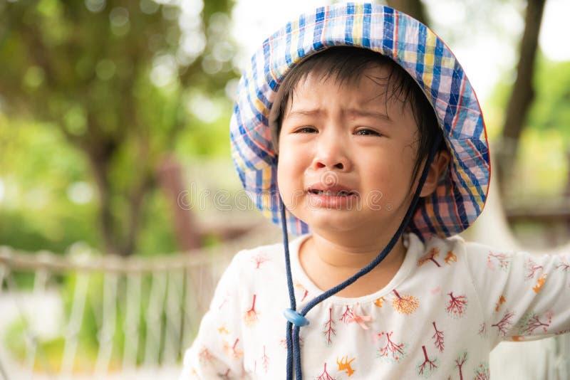 Petite fille mignonne triste pleurant dans le jardin images libres de droits