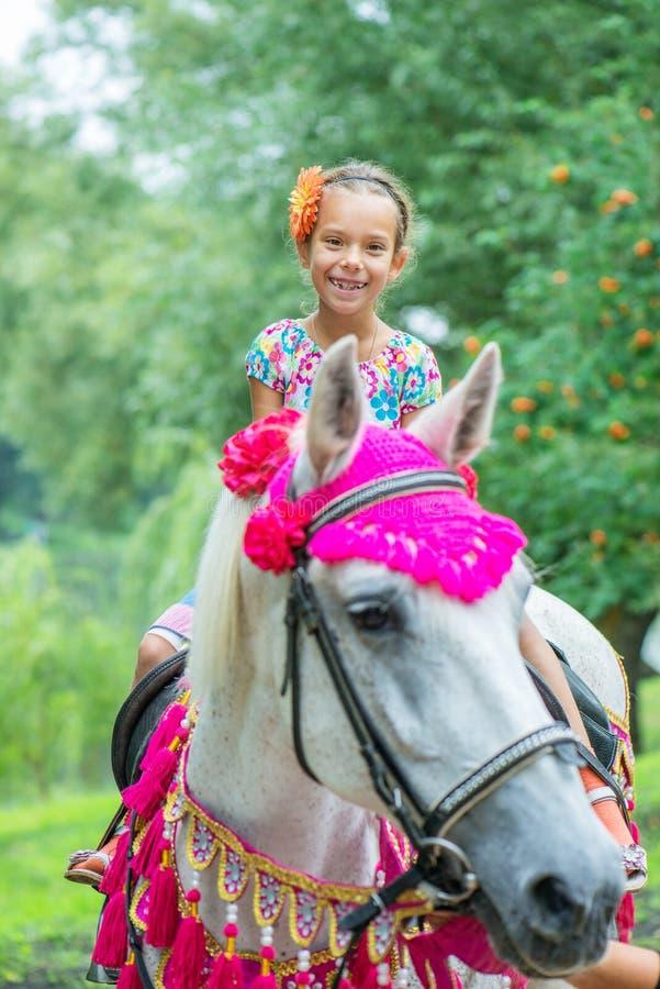 Petite fille montant le cheval de fête image stock
