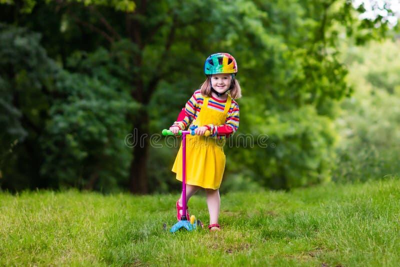 Petite fille montant un scooter coloré photographie stock