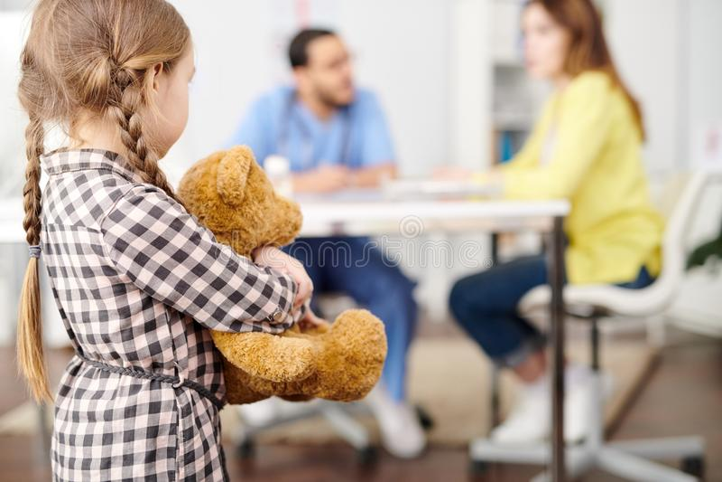 Petite fille nerveuse dans médecins Office image stock