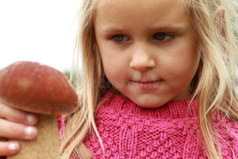 Petite fille observant le champignon de couche images stock