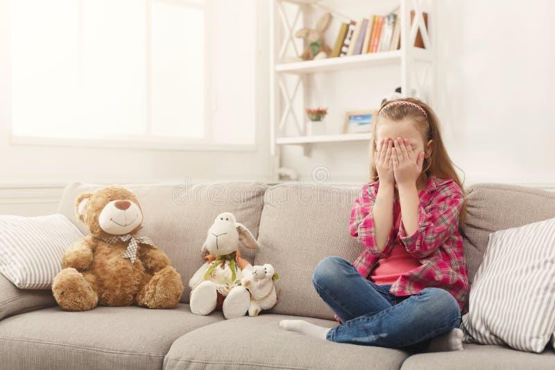 Petite fille occasionnelle effrayée regardant la TV tout en se reposant sur le sofa à la maison images stock