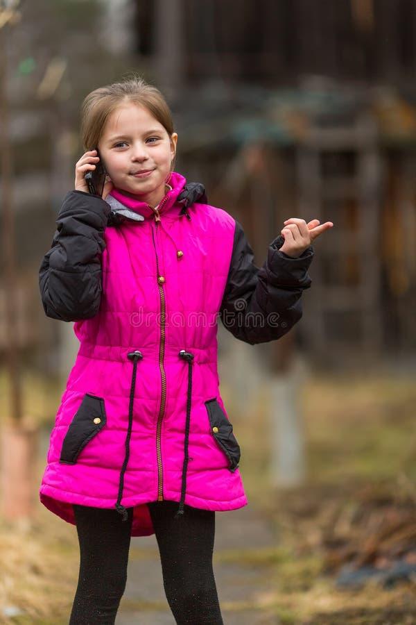 Petite fille parlant au téléphone se tenant dans la cour heureux images libres de droits