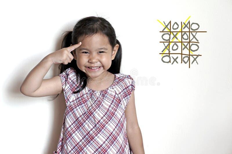 Petite fille pensant au jeu de xo images libres de droits