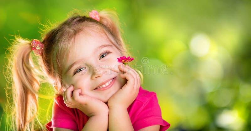 Petite fille pensant avec la marguerite image stock