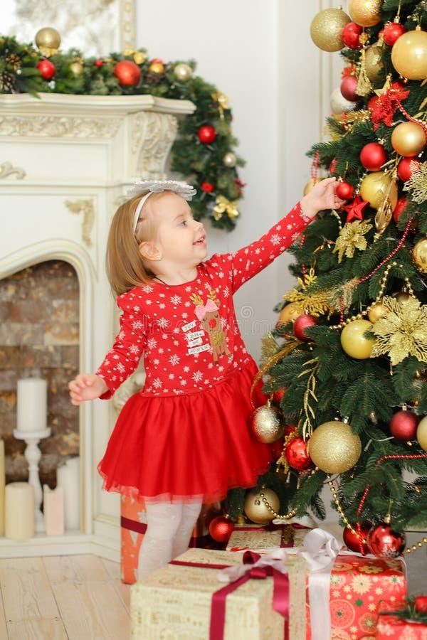 Petite fille portant la robe rouge décorant l'arbre de Noël près de la cheminée et des présents photographie stock libre de droits