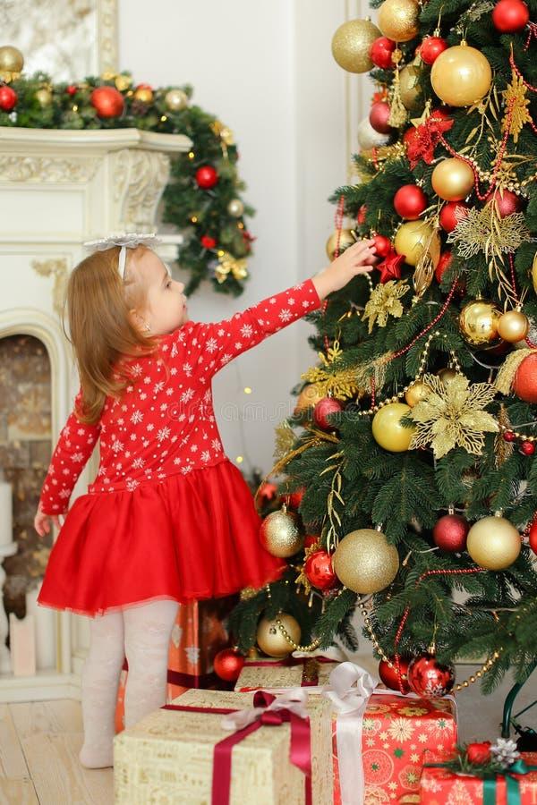 Petite fille portant la robe rouge décorant l'arbre de Noël près de la cheminée et des présents images libres de droits