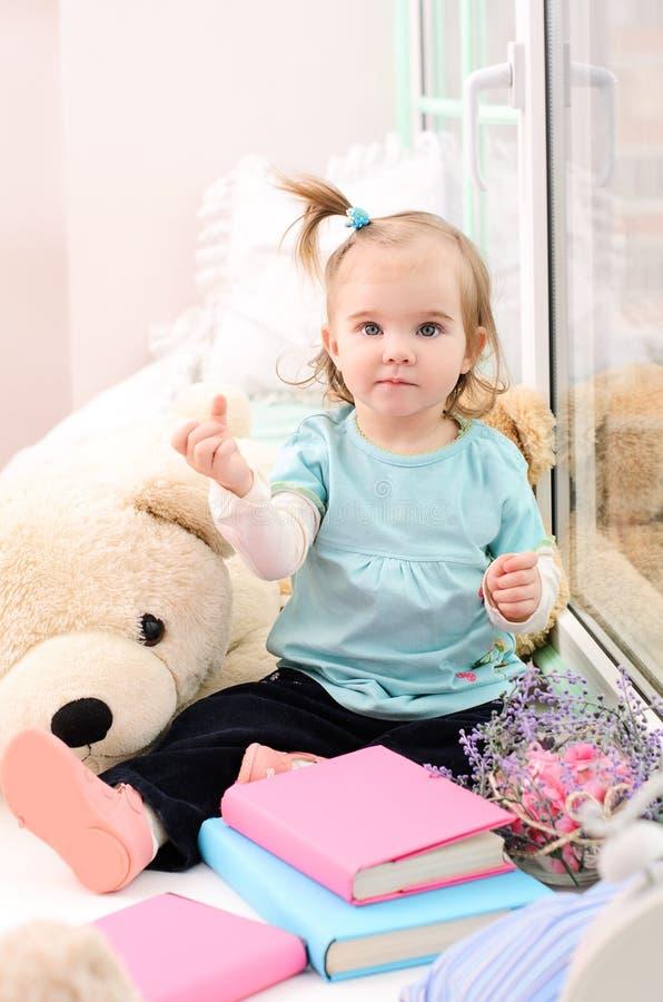 petite fille près de la fenêtre avec des livres photo libre de droits