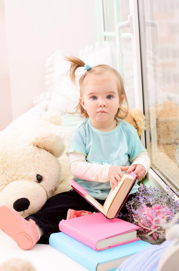 petite fille près de la fenêtre avec des livres images stock