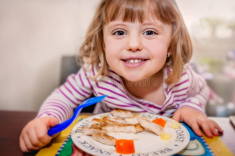 Petite fille prenant le déjeuner photo stock