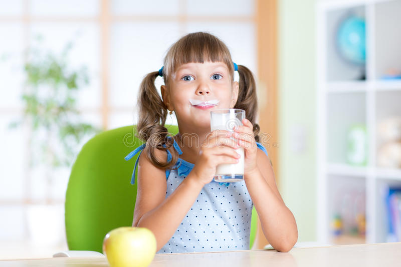 Petite fille prenant le petit déjeuner : boire d'un verre de images libres de droits