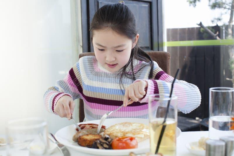 Petite fille prenant un grand petit déjeuner photo libre de droits