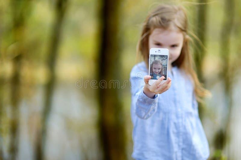 Petite fille prenant une photo d'elle-même photographie stock libre de droits