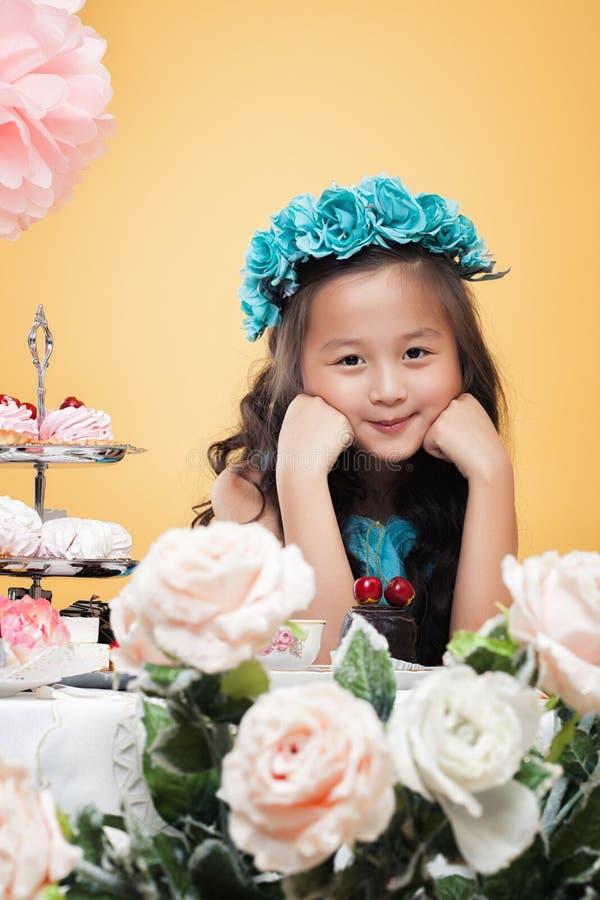 Petite fille rêveuse posant avec des fleurs, plan rapproché photographie stock libre de droits