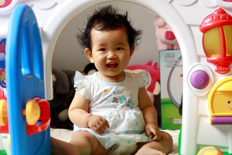 Petite fille regardant dehors d'une porte de jouet image stock