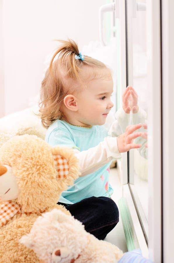 Petite fille regardant la fenêtre image stock