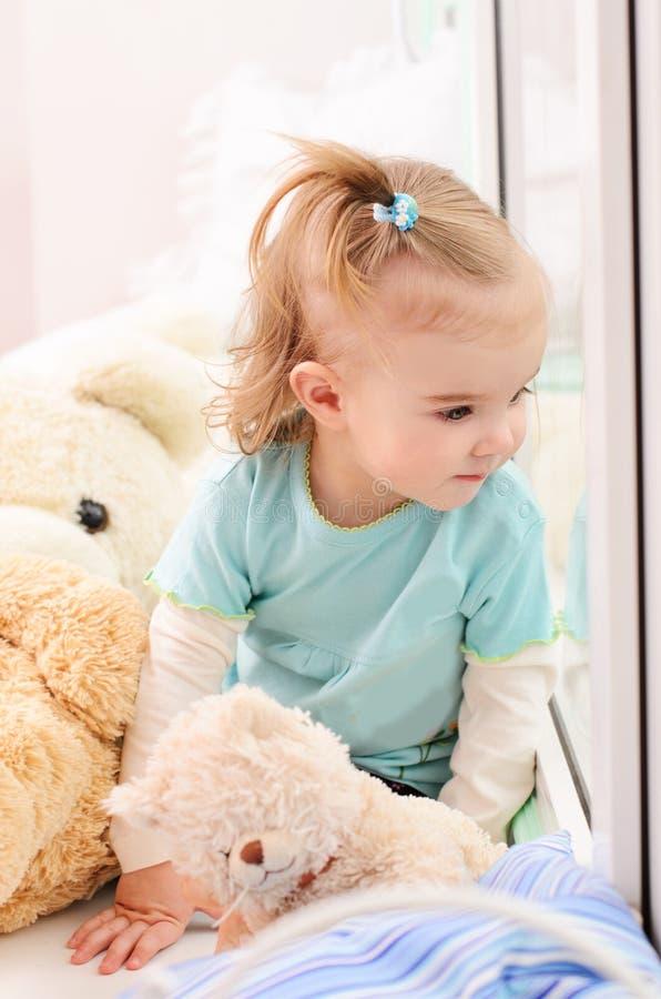 Petite fille regardant la fenêtre photos libres de droits