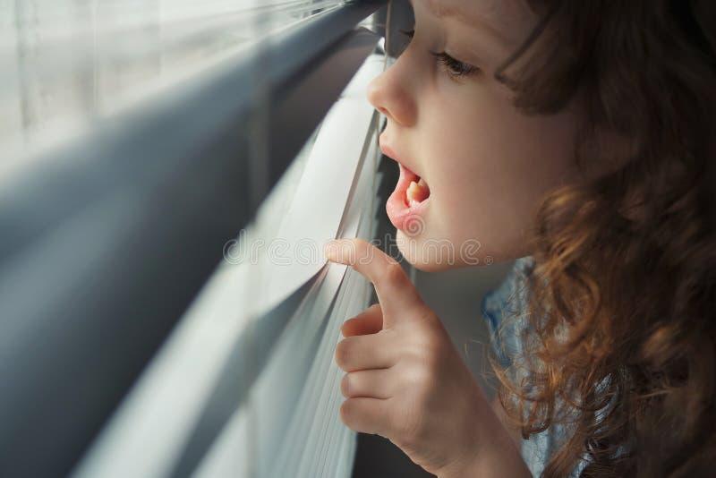 Petite fille regardant la fenêtre et pleurer image stock