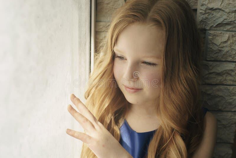 Petite fille regardant la fenêtre par les abat-jour photographie stock libre de droits