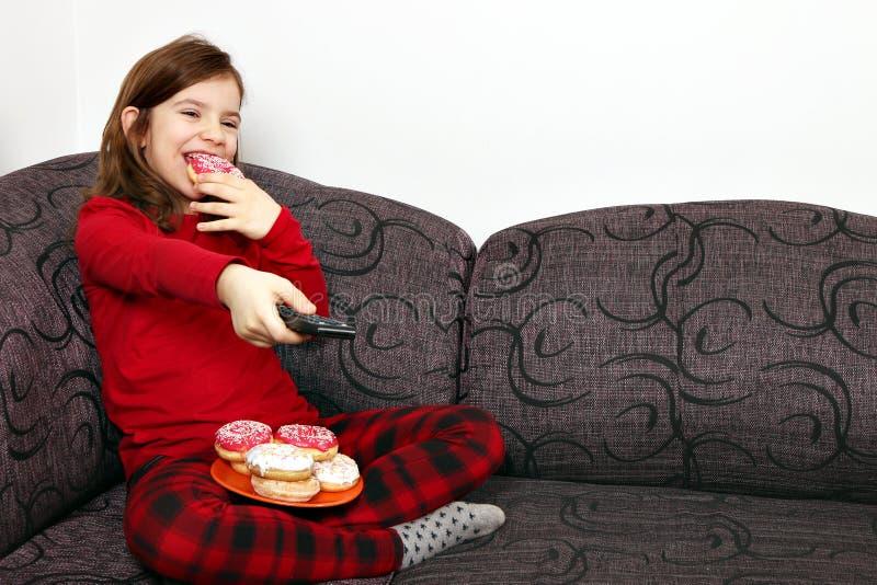 Petite fille regardant la TV et mangeant des butées toriques images stock