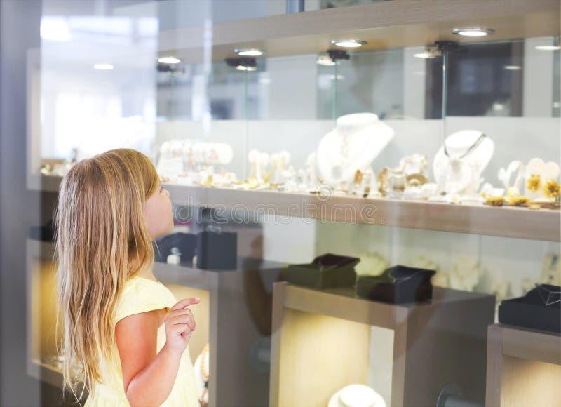 Petite fille regardant sur l'étalage photographie stock