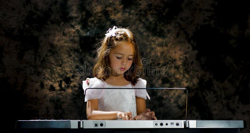 Petite fille regardant vers le bas le clavier photos libres de droits
