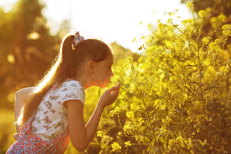 Petite fille reniflant une fleur jaune images stock
