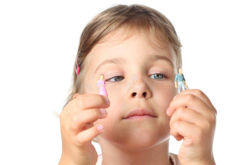 Petite fille retenant de petits chiffres de jouet des gens photo stock