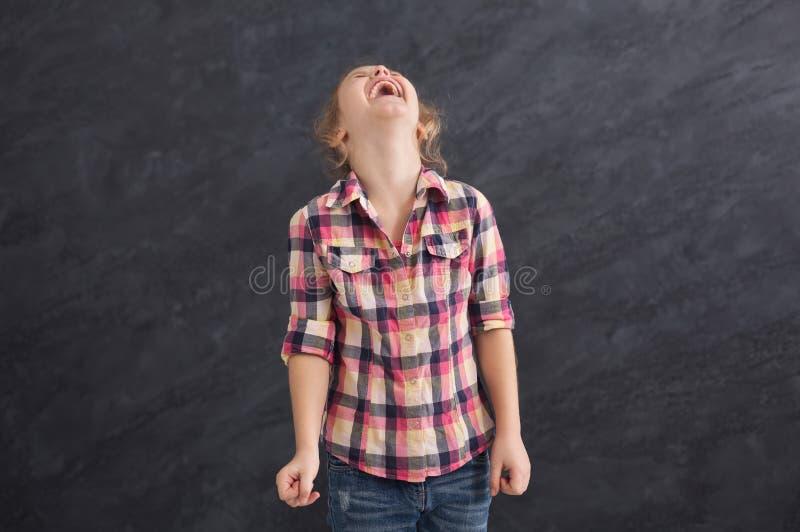 Petite fille riant du fond gris images libres de droits