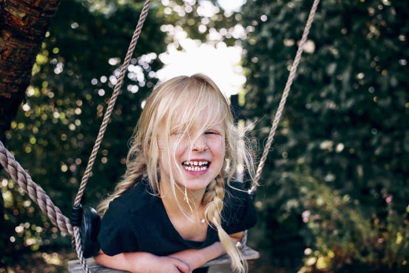 Petite fille riante jouant sur un extérieur d'oscillation d'arbre image libre de droits