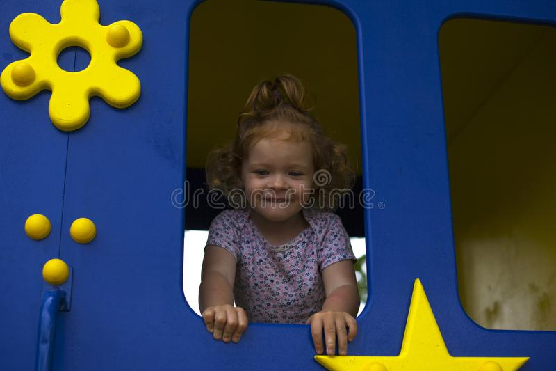 Petite fille rousse dans une maison en bois pour des enfants sur le terrain de jeu images libres de droits