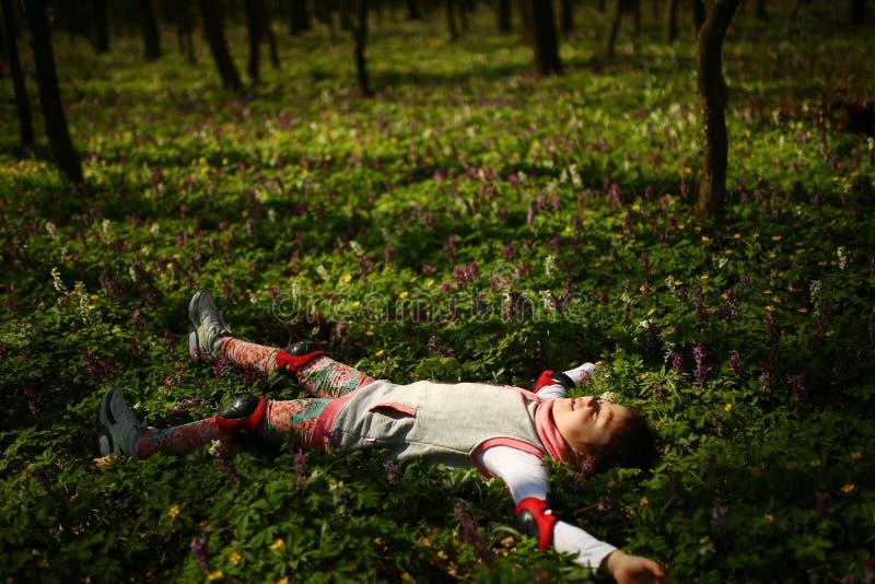 Petite fille s'étendant sur la prise de masse verte image stock