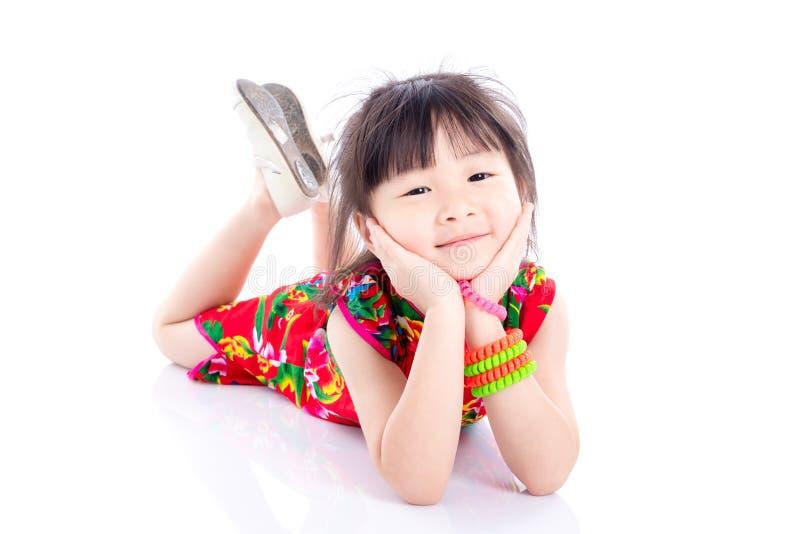 Petite fille s'étendant sur le plancher et le sourire photos stock