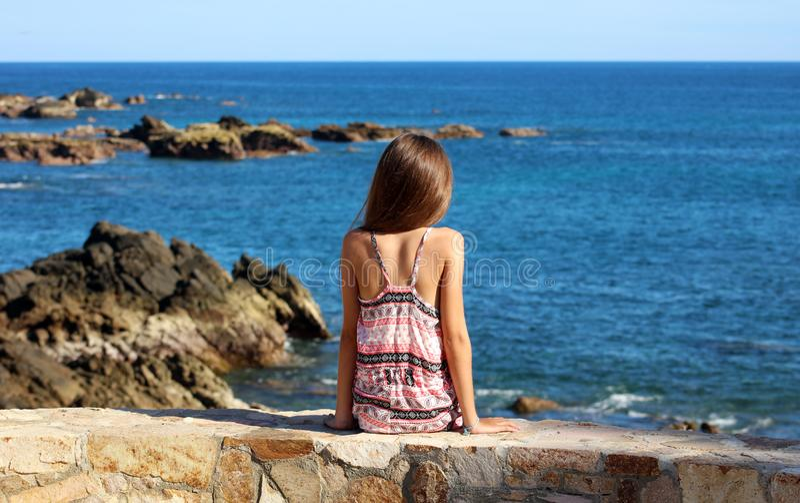 Petite fille s'asseyant à la falaise à l'avant le bord de l'océan en mer de falaise de station de vacances de Los Cabos Mexique image stock