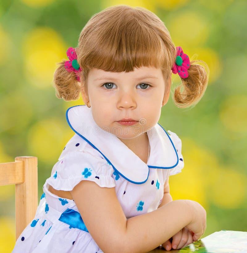 Petite fille s'asseyant à un bureau et regardant dans photo stock