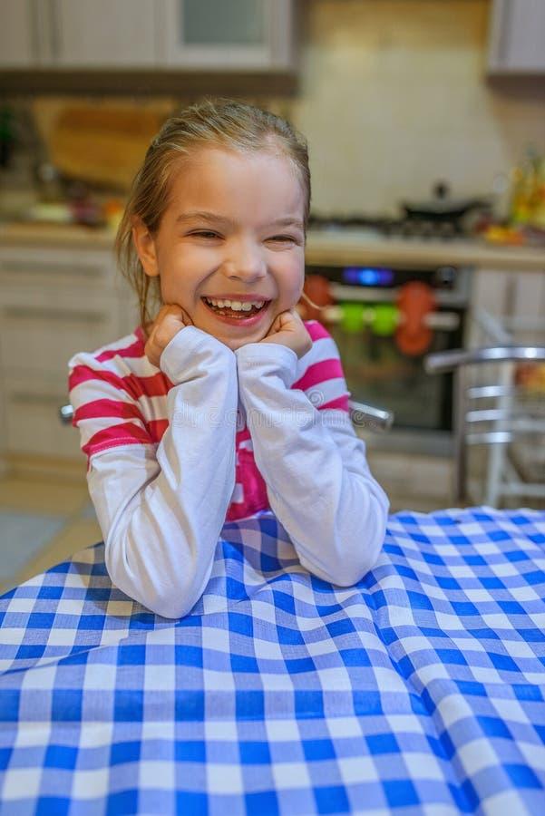 Petite fille s'asseyant à une table avec un tissu bleu photos stock