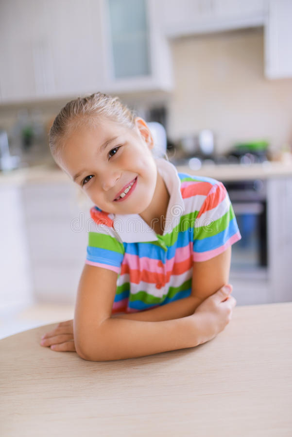 Petite fille s'asseyant à une table et à un sourire photo libre de droits