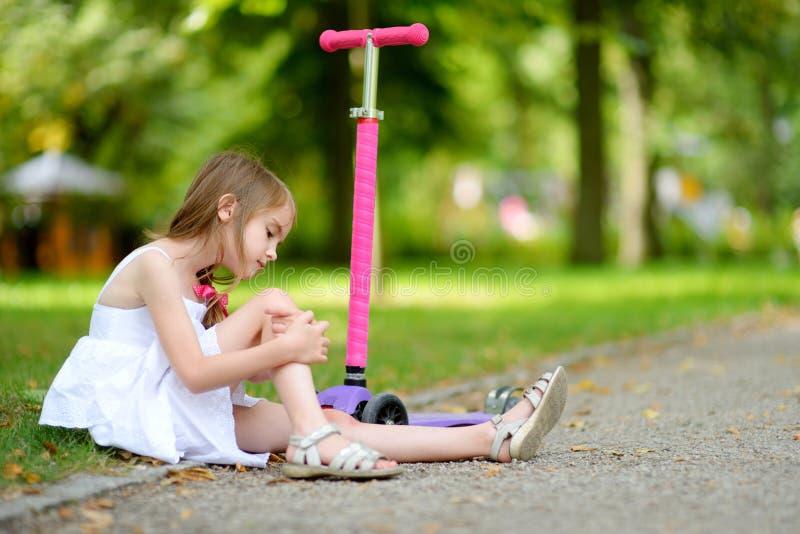 Petite fille s'asseyant au sol après qu'elle soit tombée tout en montant son scooter photographie stock libre de droits