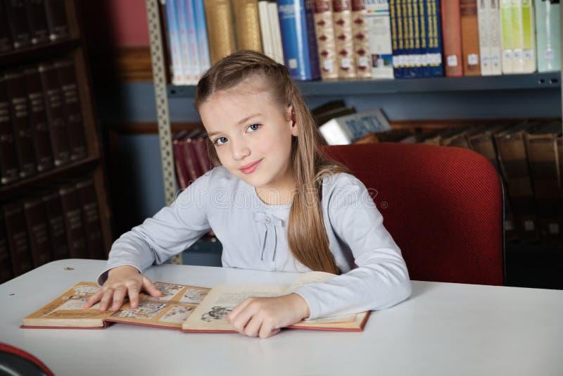 Petite fille s'asseyant au Tableau avec des livres photographie stock libre de droits