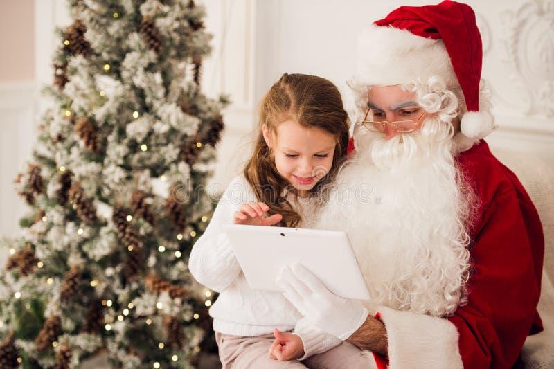 Petite fille s'asseyant avec Santa à l'aide du comprimé sur le salon de fauteuil à la maison photo libre de droits