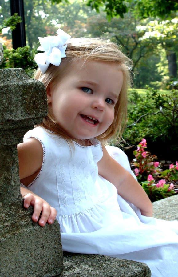 Petite fille s'asseyant dans le jardin photos stock
