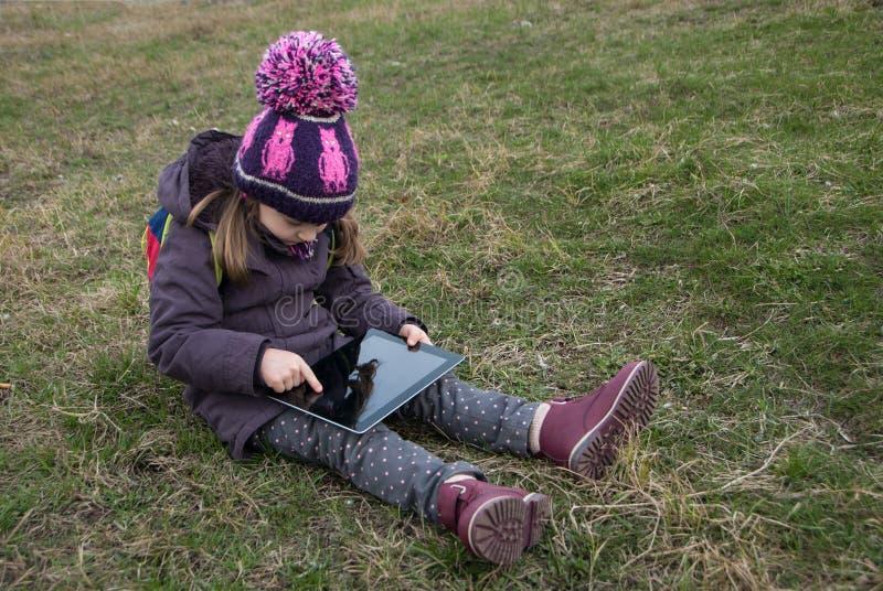 Petite fille s'asseyant en parc sur l'herbe touchant avec le doigt son instrument numérique photo stock