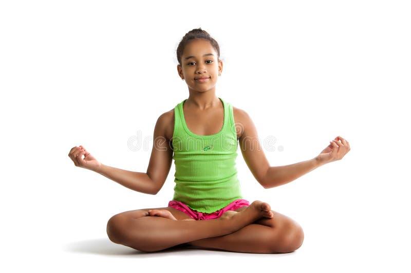 Petite fille s'asseyant en position de lotus et mains d'isolement sur le fond blanc images stock