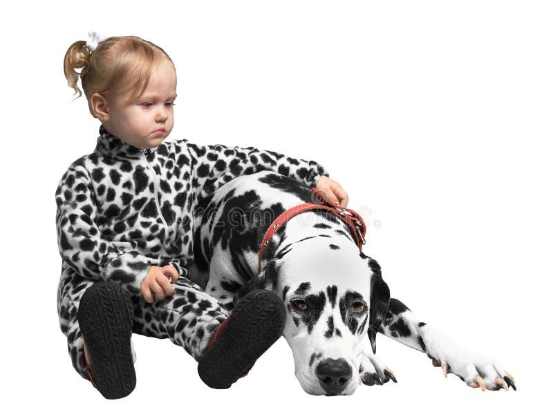 Petite fille s'asseyant près du chien dalmatien images stock